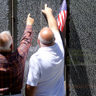 Photo by Sheldon Carpenter. Two gentlemen look at the names on the Vietnam Memorial.